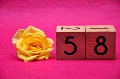 Number fifty eight with a yellow rose. On a pink background stock photo