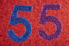 Number fifty-five blue purple over a red background. Anniversary royalty free stock images