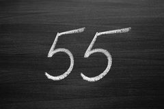 Number fifty five enumeration written with a chalk on the blackboard Stock Image