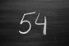Number fifty four enumeration written with a chalk on the blackboard Royalty Free Stock Images