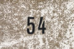 The Number 54, fifty four, on a surface with lichen.  Stock Photo