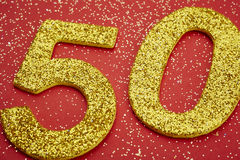 Number fifty golden color over a red background. Anniversary Stock Images