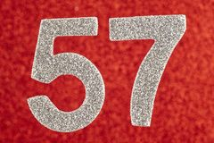 Number fifty-seven silver color over a red background. Anniversary stock images