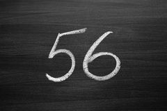 Number fifty six enumeration written with a chalk on the blackboard Stock Images