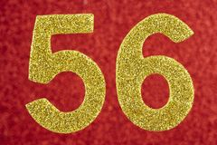 Number fifty-six golden color over a red background. Anniversary royalty free stock images