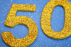Number fifty yellow color over a blue background. Anniversary. Horizontal Royalty Free Stock Images