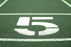 Number five. Big white track number on red rubber racetrack. Gentle textured running racetracks in stadium. Royalty Free Stock Image