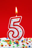 Number five birthday candle. On red background Stock Images