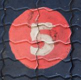 The number five in a circle is on the footpath playground. This is the number five what has painted on bricks stock images