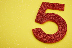 Number five red color over a yellow background. Anniversary Royalty Free Stock Image