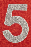Number five silver color over a red background. Anniversary. Royalty Free Stock Photo