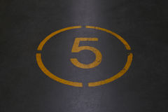 Number five is written with yellow paint Royalty Free Stock Photo