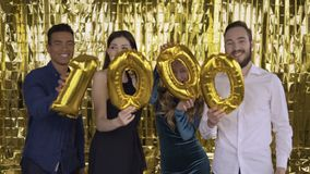 The number 100 of foil. 4 happy cheerful people at a party with balloons in their hands. A group of laughing people of stock footage