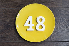Number forty eight on the yellow plate. Number forty eight on the plate yellow and brown background royalty free stock photos