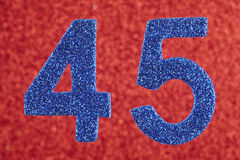 Number forty-five blue color over a red background. Anniversary. Stock Photos
