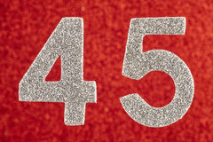 Number forty-five silver color over a red background. Anniversar Royalty Free Stock Photos
