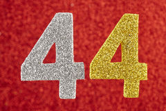 Number forty-four silver yellow color over a red background. Ann Stock Photography