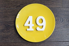 Number forty nine on the yellow plate. Number forty nine on the yellow plate and brown background Stock Image