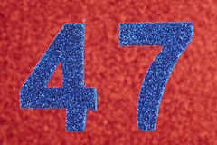 Number forty-seven blue color over a red background. Anniversary Stock Photos