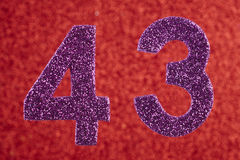 Number forty-three purple color over a red background. Anniversa royalty free stock photo