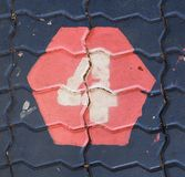 The number four in a hexagon is on the footpath playground. This is the number four what has painted on bricks royalty free stock image