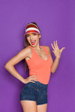 It Is Number Four. Shouting girl in orange shirt and sun visor showing four fingers. Three quarter length studio shot on violet background Royalty Free Stock Photos