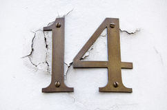 Number fourteen on cracked wall. Brass figures for the number fourteen screwed to a plastered wall which is cracking.  Outside pillar of a building in central Royalty Free Stock Photo