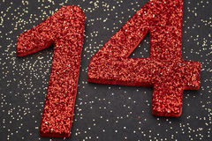 Number fourteen red color over a black background. Anniversary Royalty Free Stock Photos