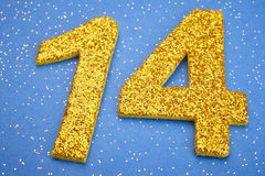 Number fourteen yellow color over a blue background. Anniversary Stock Photo