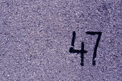 Number fourty seven on blue plaster wall. Stock Photos