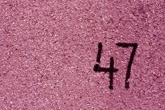 Number fourty seven on pink plaster wall. Royalty Free Stock Images