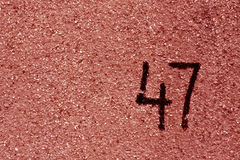 number fourty seven on red plaster wall. Royalty Free Stock Photo