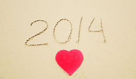 Number 2014 and Heart shape on the beach Royalty Free Stock Photos