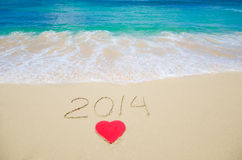 Number 2014 and heart shape on the beach Royalty Free Stock Photo