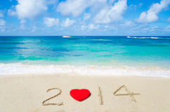 Number 2014 with heart shape on the sandy beach Royalty Free Stock Photography