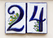 Number 24. House number in Amsterdam, made in the traditional delftware style, with blue and white tin glaze, decorated with calla lilies Royalty Free Stock Photos