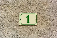 Number 1. House number one 1 on a plastered wall Stock Image
