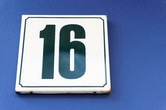 Number. House number sixteen slab on a blue house wall Stock Photography