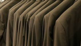 Number of identical-colored men`s suits hanging on a hanger in a clothing store in a mall. A number of identical-colored men`s suits hanging on a hanger in a stock video footage