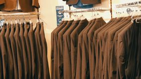 Number of identical-colored men`s suits hanging on a hanger in a clothing store in a mall. A number of identical-colored men`s suits hanging on a hanger in a stock video