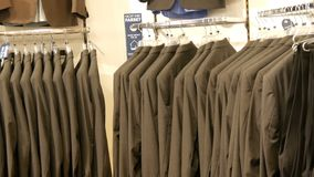 Number of identical-colored men`s suits hanging on a hanger in a clothing store in a mall. A number of identical-colored men`s suits hanging on a hanger in a stock footage
