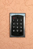Number Keypad. Numbers 1 through 9 on a keypad mounted on an salmon ccolored stucco wall royalty free stock photography