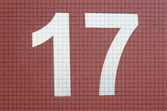 Number 17. Label number 17 in white wall stuck in brown or reddish royalty free illustration