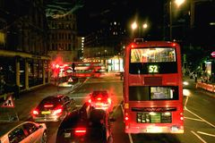 London traffic at night. Number 52 London double decker bus, taxi and cars in three lanes held up by traffic lights at night royalty free stock photo