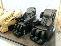 A number of massage leather electric chairs in different colors.