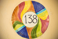 Number 138 in the middle of multicolored ceramic circle on the l Stock Image
