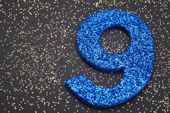 Number nine blue color over a black background. Anniversary Royalty Free Stock Photos