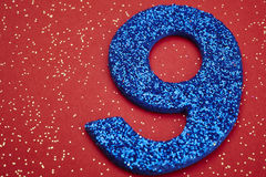 Number nine blue color over a red background. Anniversary Stock Photos