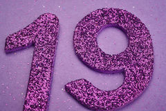 Number nineteen purple color over a purple background. Anniversa Royalty Free Stock Photo