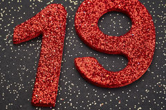 Number nineteen red color over a black background. Anniversary Royalty Free Stock Photo